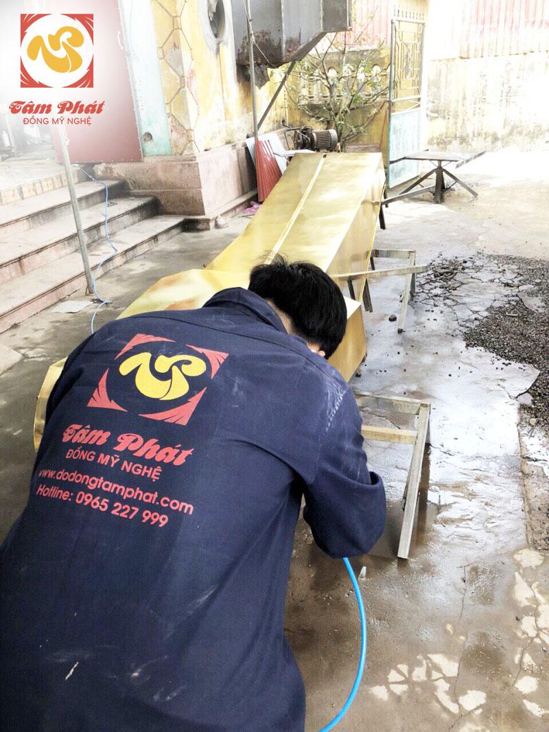 Nghệ nhân của đồ đồng Tâm Phát đang tiến hành mạ vàng một cạnh của công trình Tượng Đài